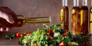 A man pours olive oil on a healthy salad