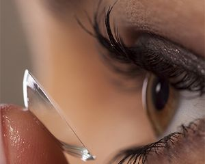 A closeup photograph of a woman putting a contact lens in her eye. The contact is on her fingertip and approaching her eye.