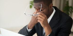 A man in a business suit rubs his eyes while holding his glasses and sitting in front of a laptop computer.