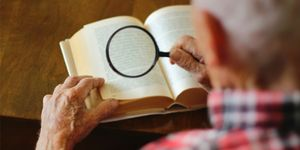 Overhead view of an older man holding a magnifying glass over a book to read.