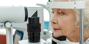 An older woman has an eye exam using a slit-lamp viewer.