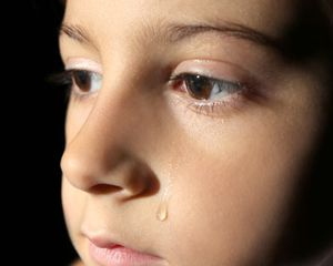 Closeup photo of a child with a tear running down his cheek, against a black studio background.