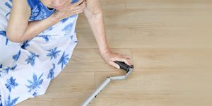 Staged image of an elderly woman with a cane who has fallen on a wooden floor.