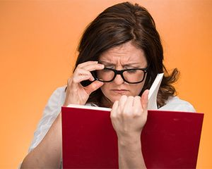 A woman is trying to read a book while wearing glasses. She is having trouble reading and her face is concerned.