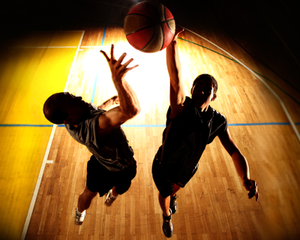 Silhouetted Basketball players jumping for ball on court
