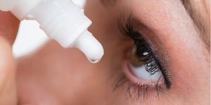 A woman holds a bottle of drops over her eye and prepares to let the drop fall into her eye.