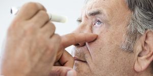 An older man has a penlight shone into his eye to check vision