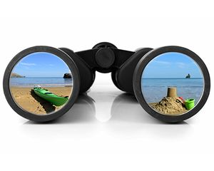 A pair of binoculars looking at a beach scene
