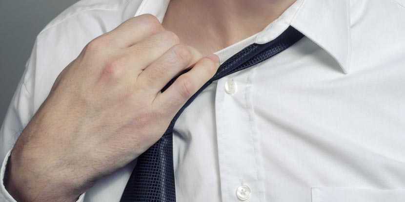 Closeup of a man's torso as he loosens a necktie that's placed over a white dress shirt.