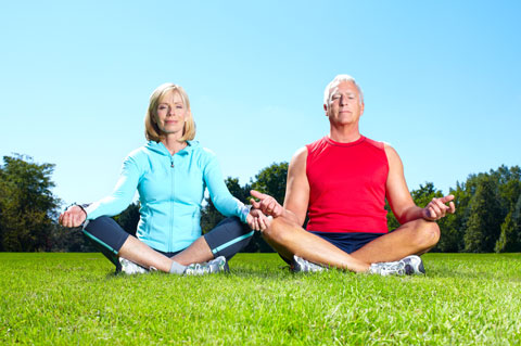 Healthy senior couple meditating in the park