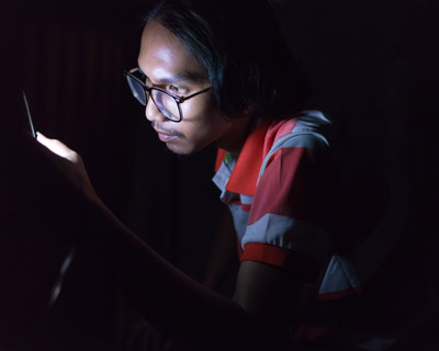 Man reading his smartphone in the dark.