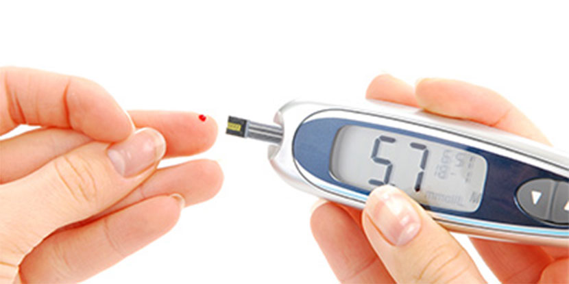 Person doing a home blood sugar test, holds a blood glucose meter and pricks a finger. A small drop of blood is on the fingertip.