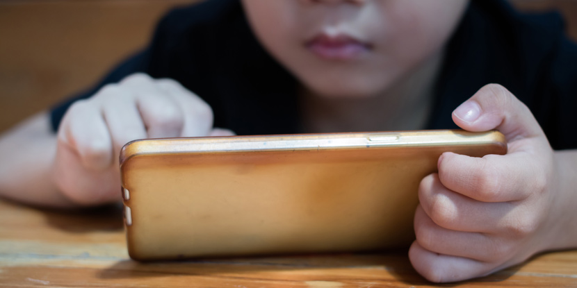 Closeup, cropped image of a young child using a smartphone on a table.