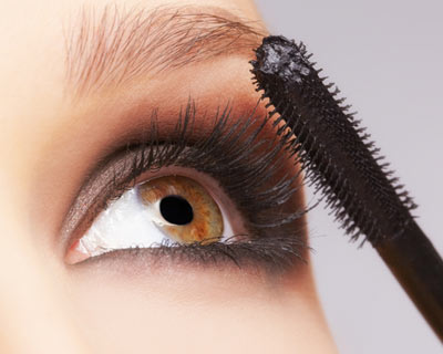 Closeup photograph of woman applying mascara makeup to eyelashes