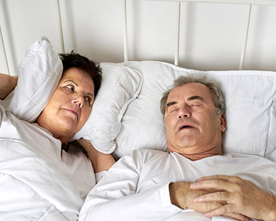 Man snoring in bed while his annoyed wife looks at him