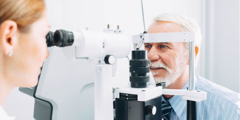 Young female ophthalmologist using slit lamp to examine older happy man