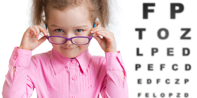 Young girl with glasses in front of eye test chart
