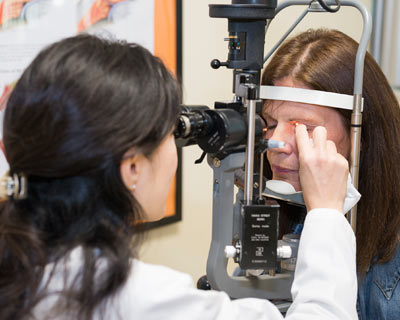 Dr. Song examines Christine in her office, using a slit lamp viewer.