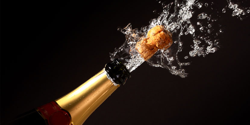 A cork flies out of a Champagne bottle, surrounded by a spray of liquid.