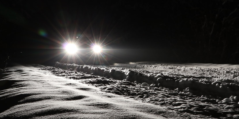 Car headlights on winter road, showing starbursts around lights.