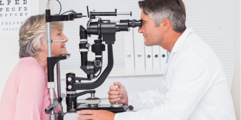 A doctor and his patient sit together at a slit lamp microscope for an exam