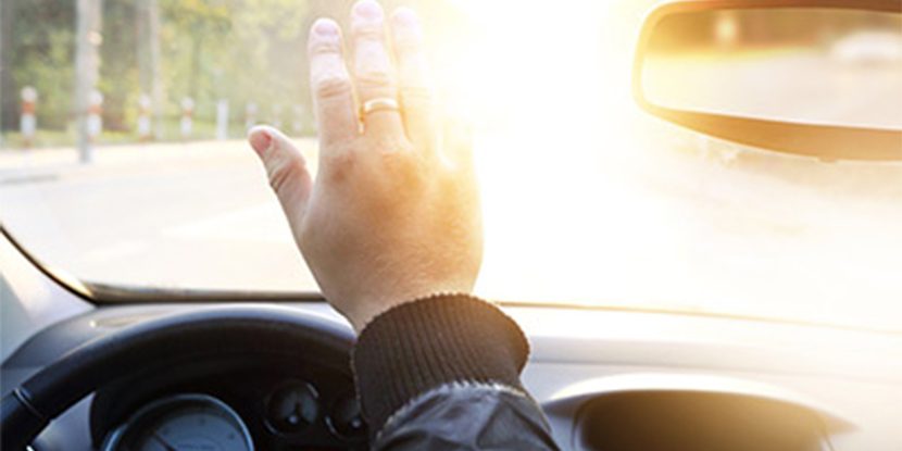 Driver blinded by sun glare holds up hand to shield eyes