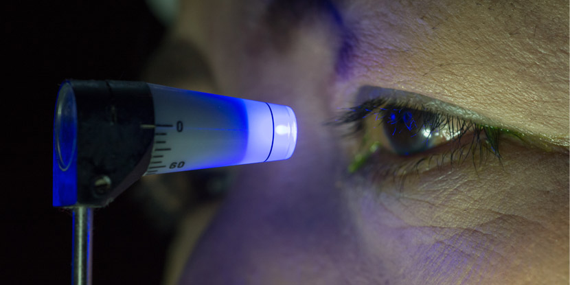 Closeup of tonometer for measuring eye pressure, with blue light near patient's eye.