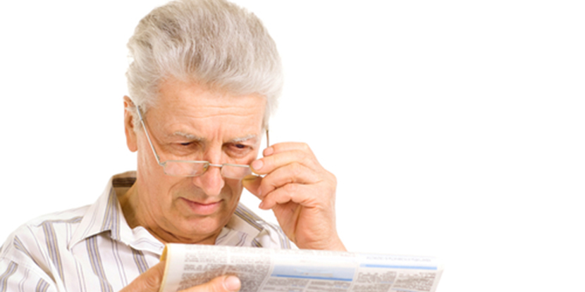 An older man is having some trouble reading a newspaper and adjusts his glasses.