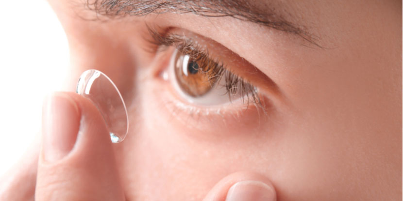 Close-up photograph of young woman putting contact lens in eye