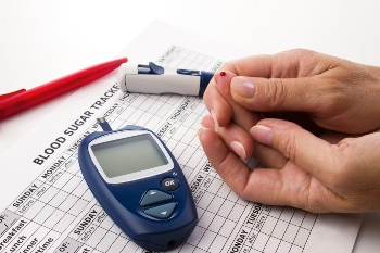 Hands and blood glucose monitor performing a blood glucose test.