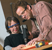 Father and son wearing eye protection while using tools