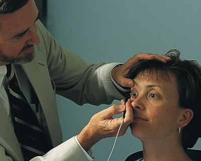 A doctor using pachymetry to measure the thickness of a woman's cornea.