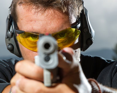 Photograph of a man wearing eye protection while shooting a gun