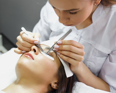 Aesthetician with tweezers applying eyelash extensions to a woman laying down, with her eyes closed.