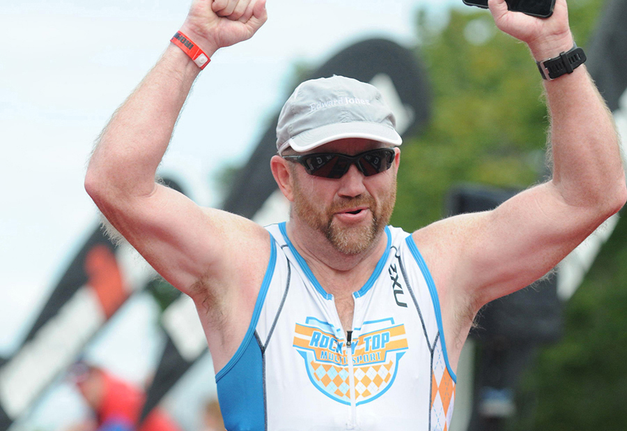 Patient Gary Stuart raises his arms in victory crossing the Ironman finish line.