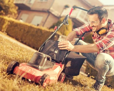 Photograph of a man kneeling by lawnmower