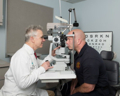 Thomas Steinemann, MD, examines firefighter Jay Northup's eyes to monitor his vision and his recovery as he continues to heal from the fireworks explosion that almost blinded him.