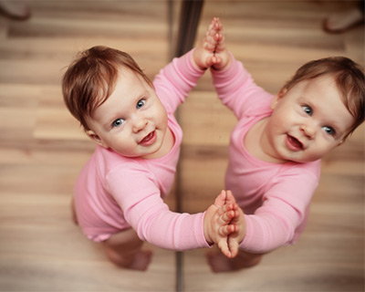Photgraph of a baby at a mirror