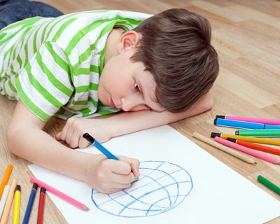 Photograph of a boy on the floor drawing a picture