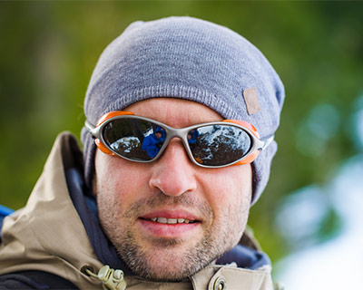 A man is wearing winter clothes and wraparound sunglasses.