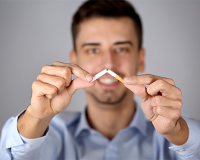 Photograph of a man breaking a cigarette