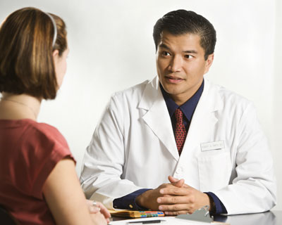 Doctor sitting at desk talking with patient