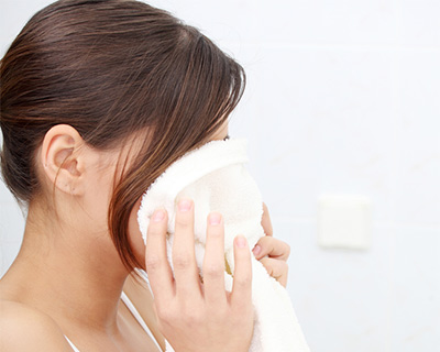 Woman drying her face with a clean white towel.