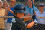 Boy in helmet and protective glasses at bat in baseball game
