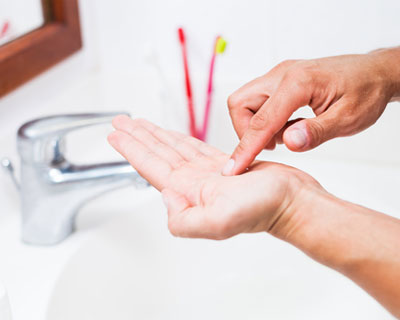 Close-up of hands cleaning a contact lens at a sink