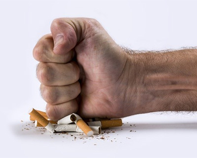 Photograph of a fist crushing cigarettes