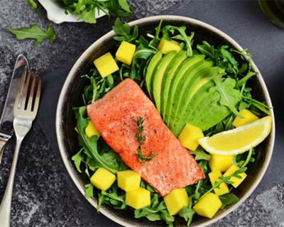 A dinner plate with salmon, salad and avocado