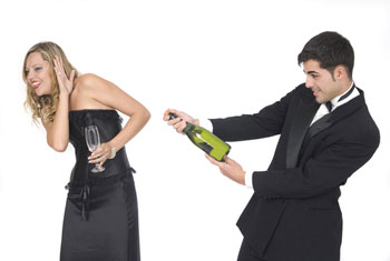 Man aiming champagne bottle at woman