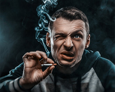 A man is smoking a cigarette and bothered by smoke in his eyes.