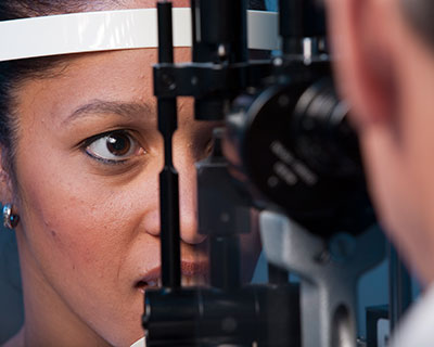 Ophthalmologist uses slit lamp to examine woman's eyes